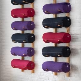 Kurma yoga bolsters stored on wooden rack
