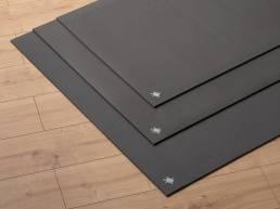 Kurma Black Grip yoga mats 3 sizes stacked on wooden floor